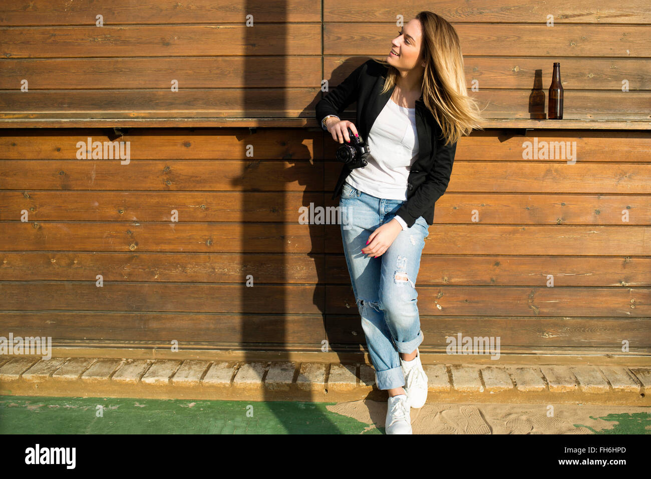 Portrait of woman with camera watching something - Stock Image
