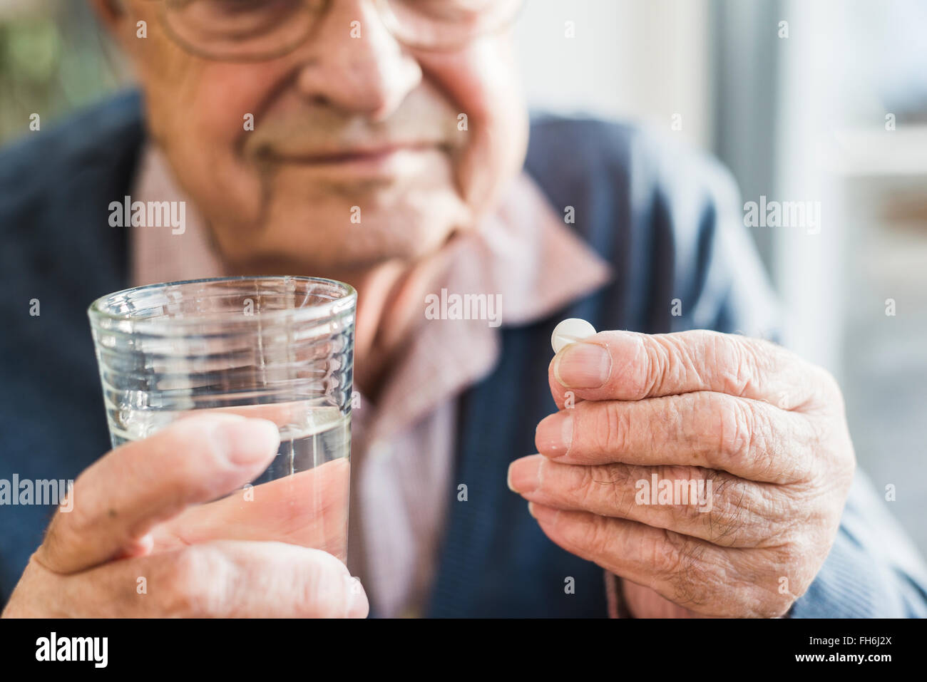 Hands of senior man holding tablet and glass of water, close up - Stock Image