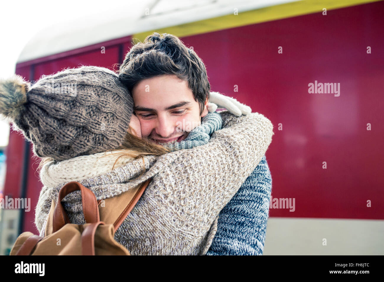 Happy young couple embracing in front of train - Stock Image
