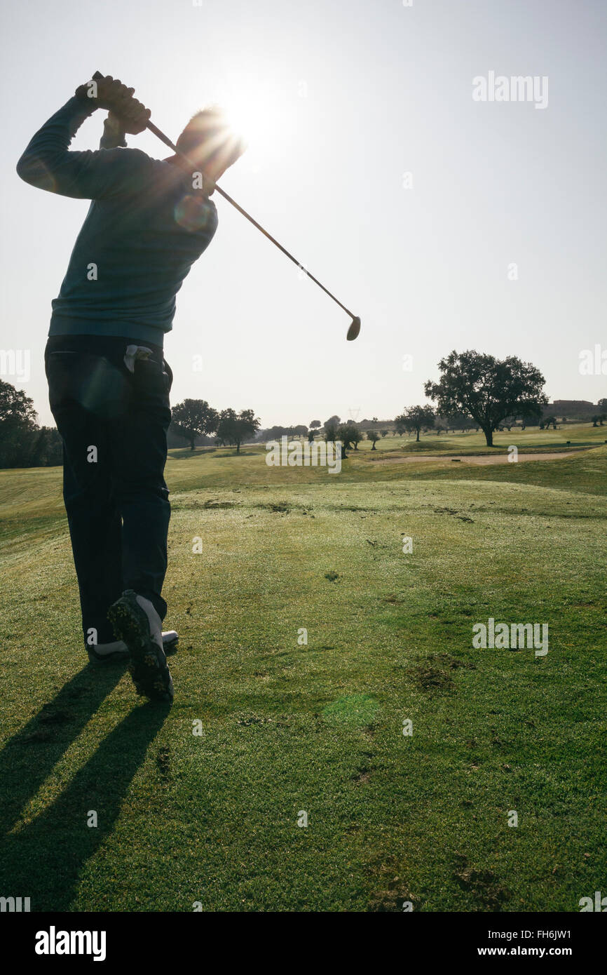 Backlighting of a golfer hitting a golf ball on a golf course - Stock Image