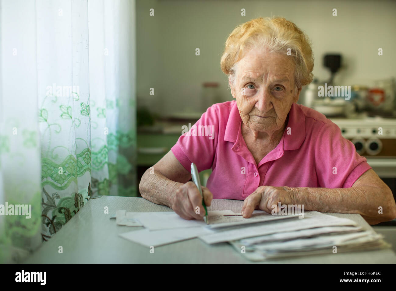 The old woman fills out utility bills sitting in the kitchen. - Stock Image