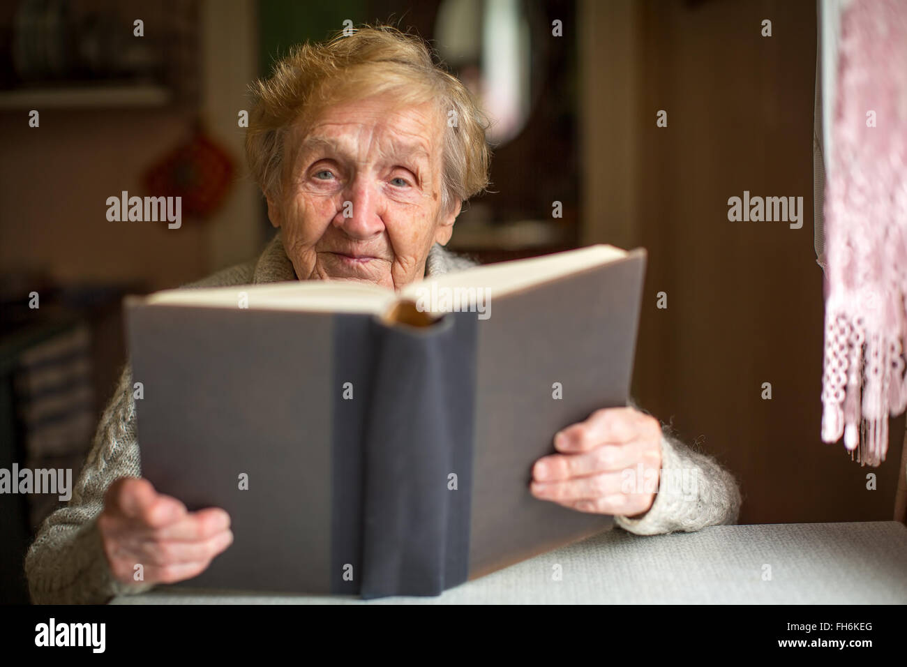 An elderly woman reading a large book. - Stock Image