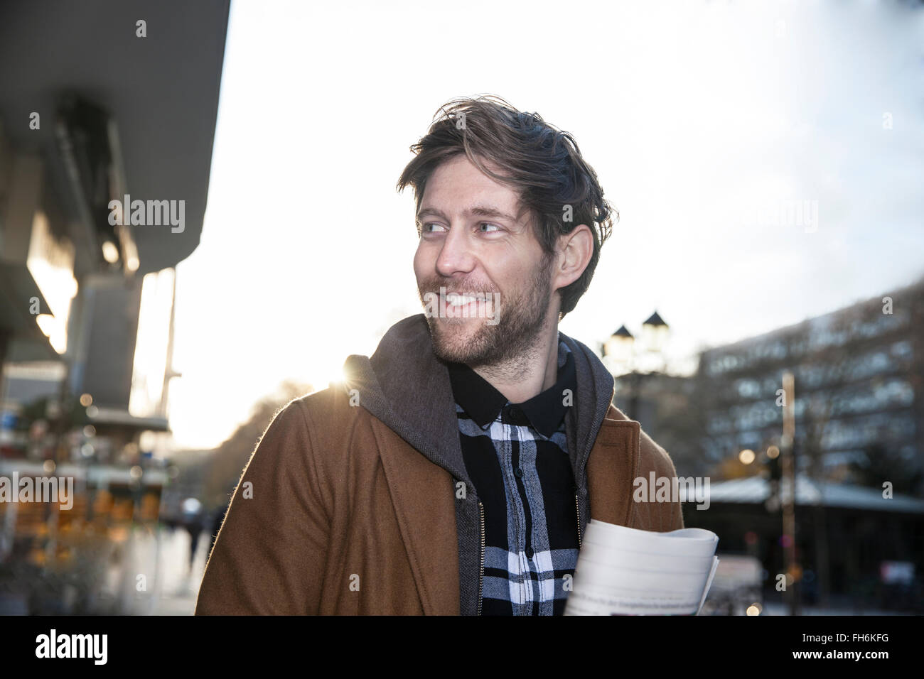 Portrait of smiling man watching something - Stock Image