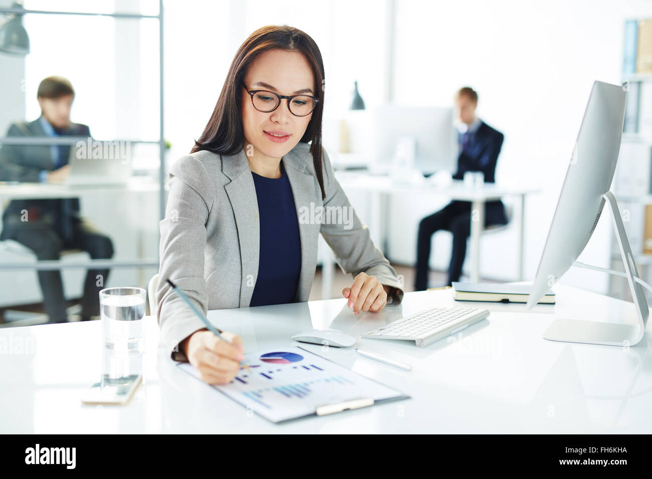 Pretty secretary analyzing data at workplace in front of computer - Stock Image
