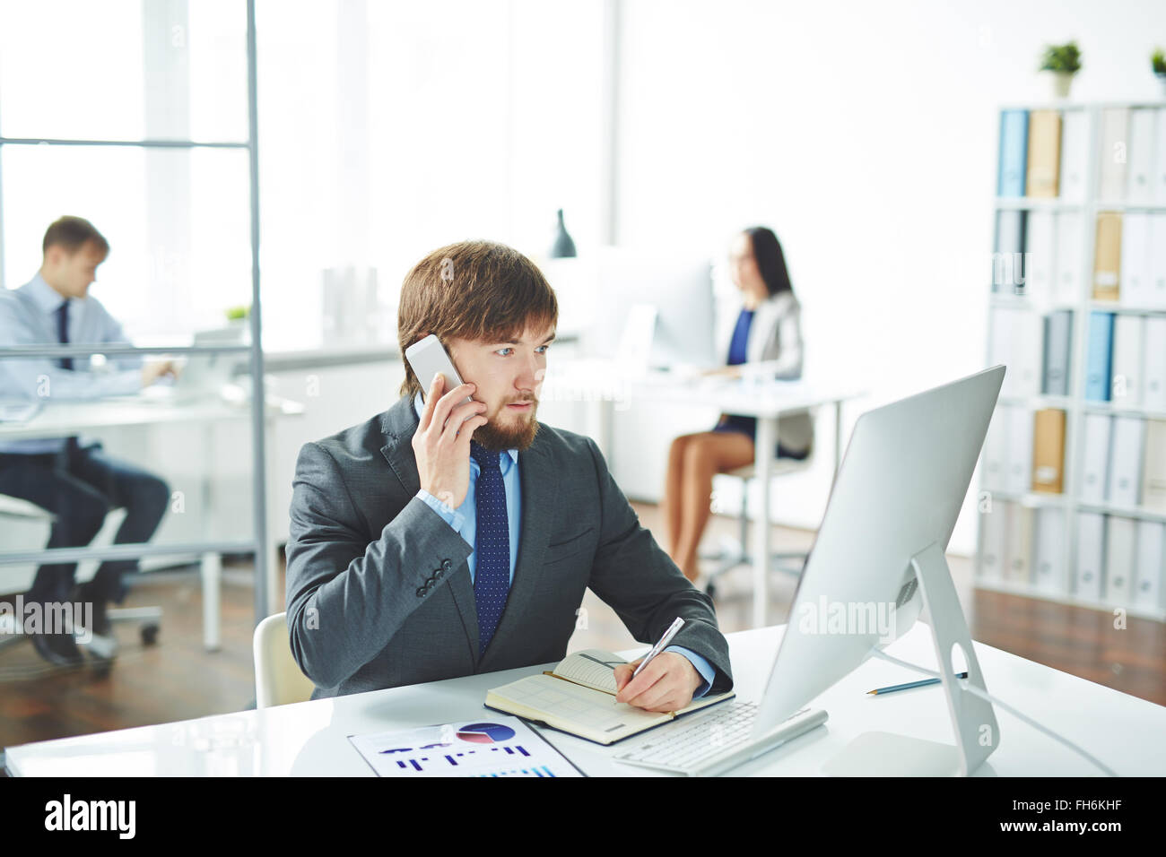 Elegant businessman calling and making notes in front of computer in office - Stock Image