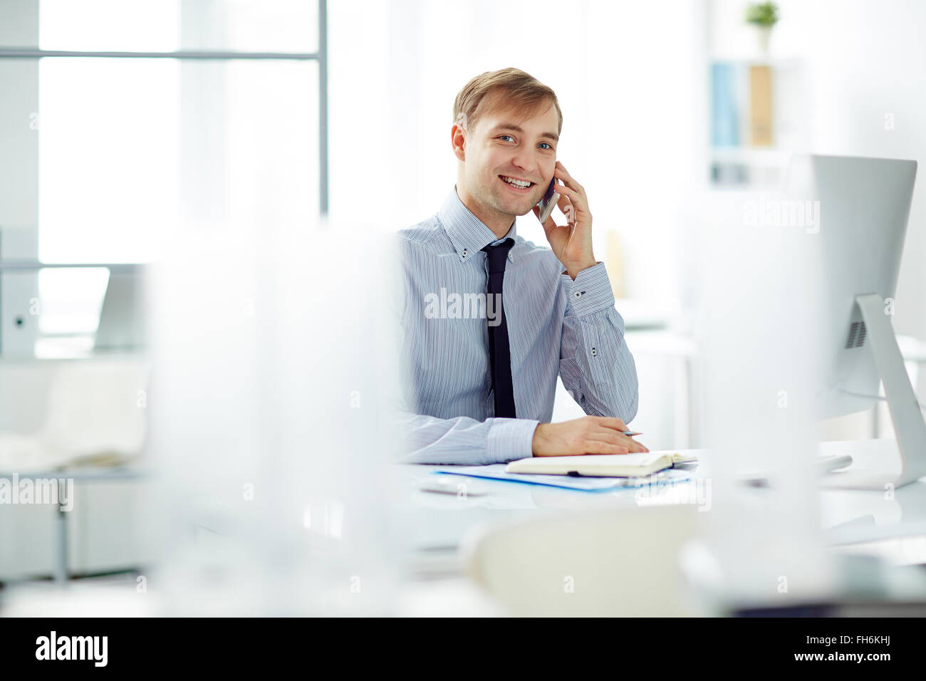 Young businessman speaking on the phone at workplace and looking at camera - Stock Image