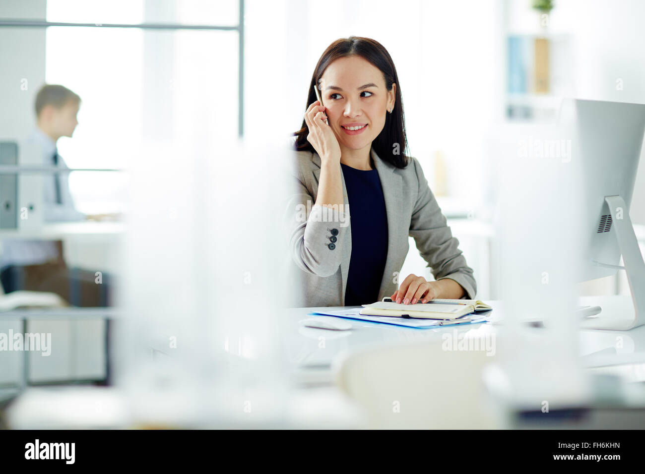 Young businesswoman speaking on the phone while planning work - Stock Image