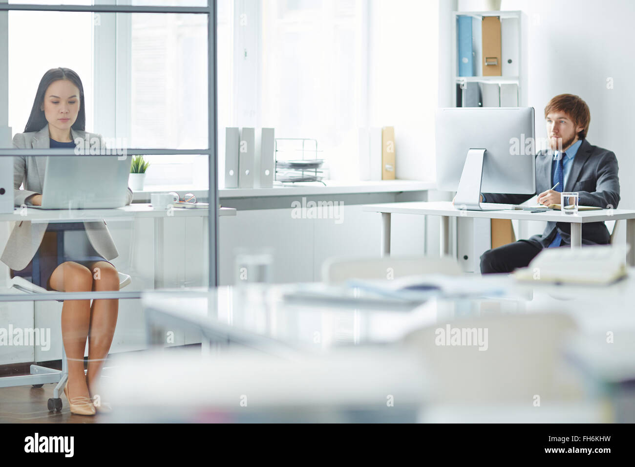 Two young managers doing their routine work in office - Stock Image