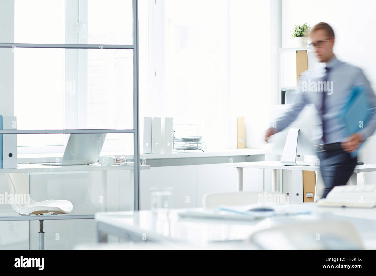 Blurred figure of office manager passing by workplace - Stock Image
