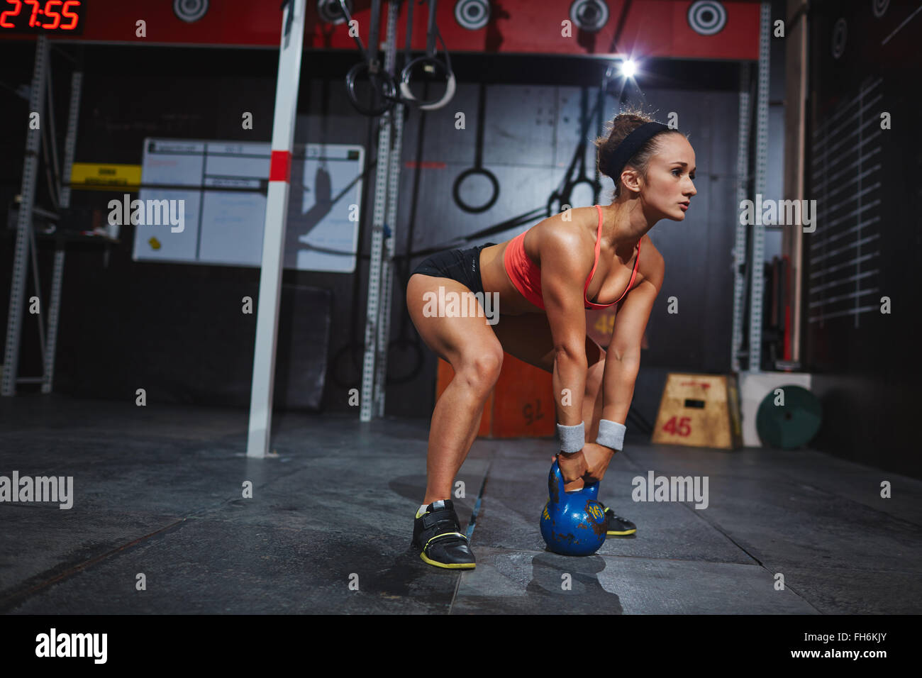 Strong young female working out with kettle - Stock Image