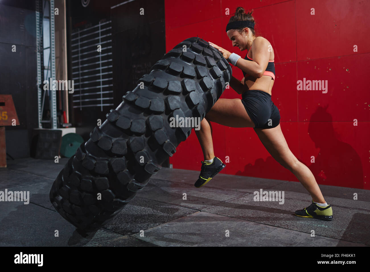 Active woman in sportswear flipping tyre in gym - Stock Image