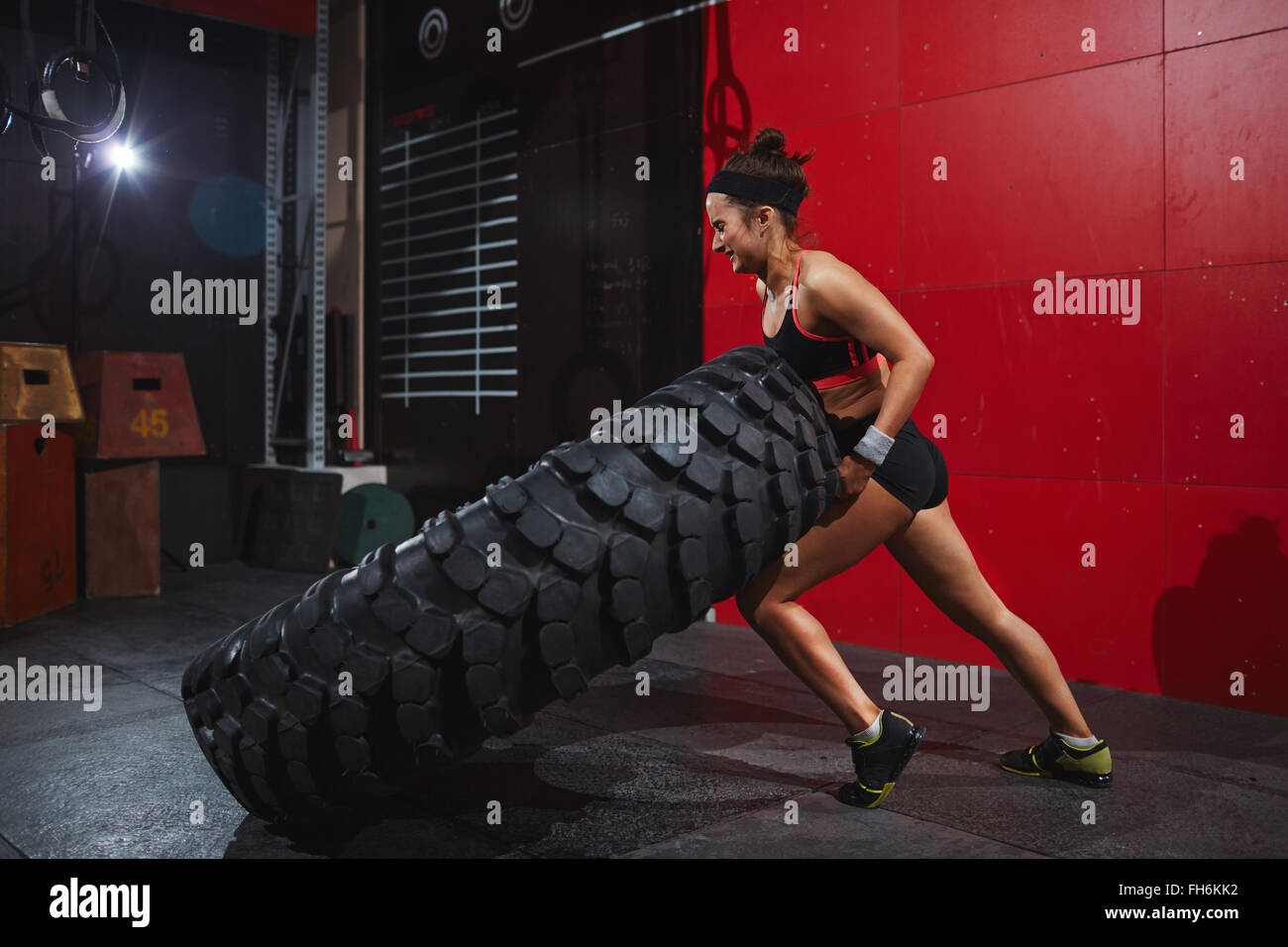 Active and strong woman flipping tyre with help of arms and knee - Stock Image