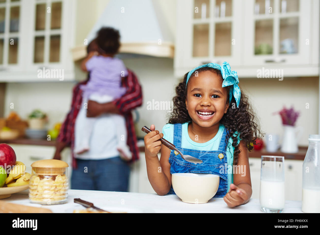 Happy African-American girl eating morning cornflakes - Stock Image