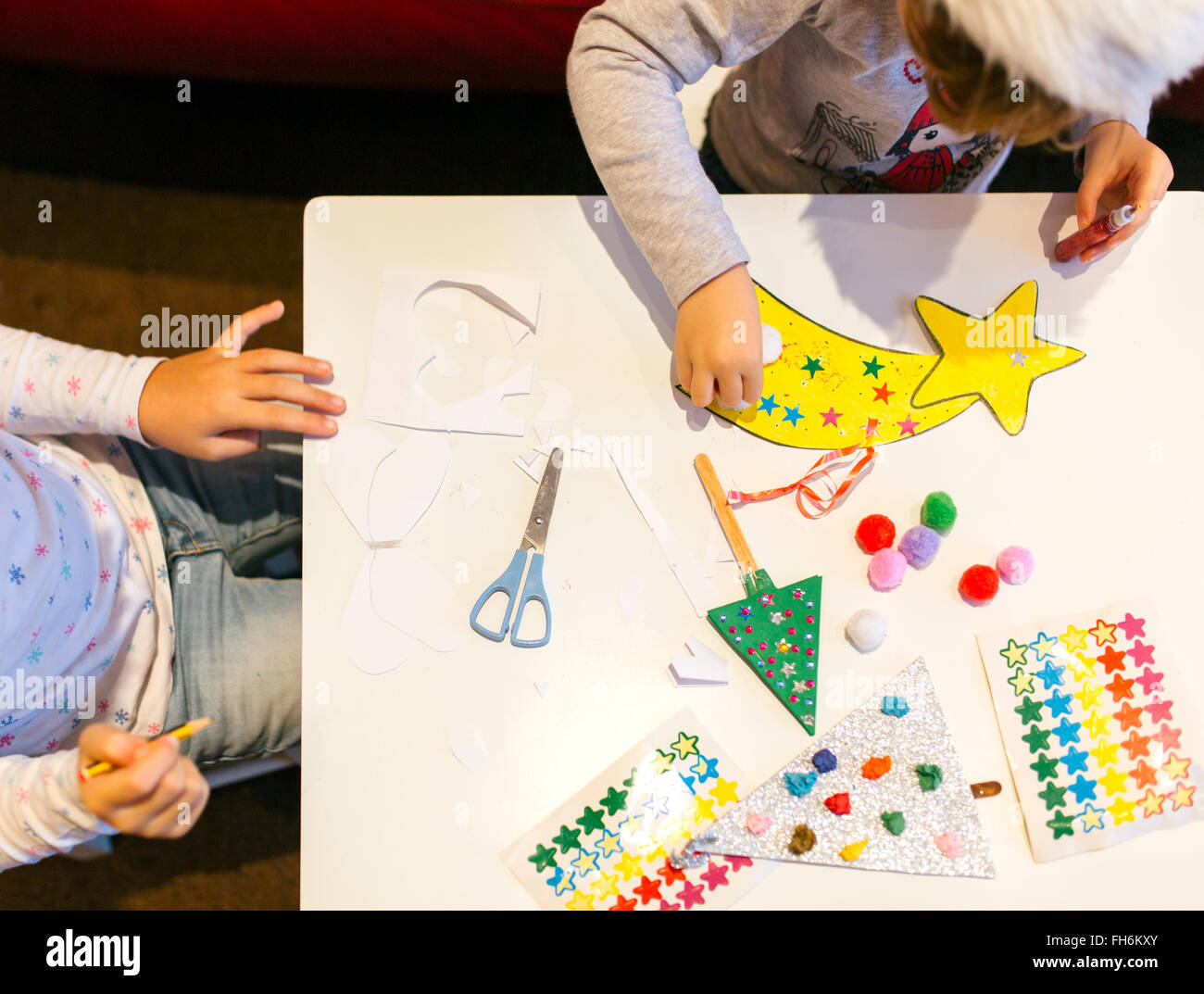 Two little girls tinkering Christmas decoration - Stock Image