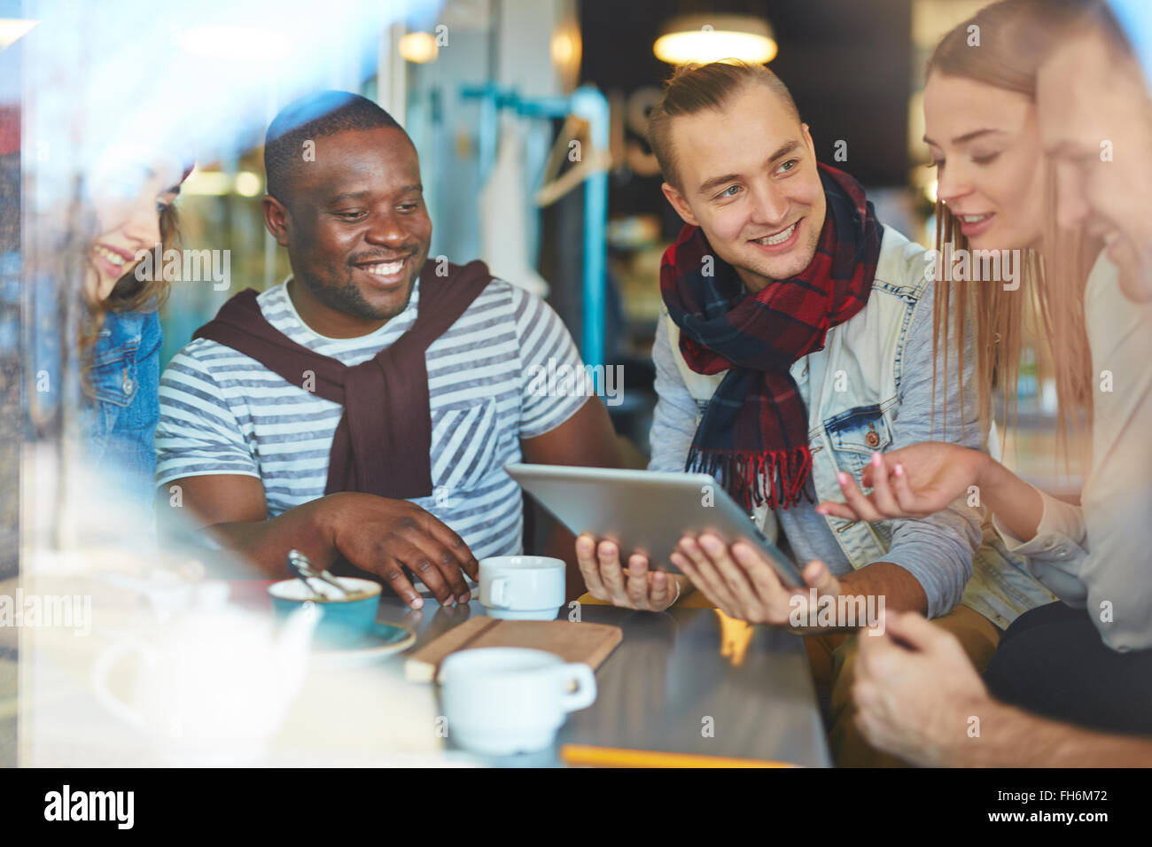 Friendly guys and girls networking and discussing data in cafe - Stock Image