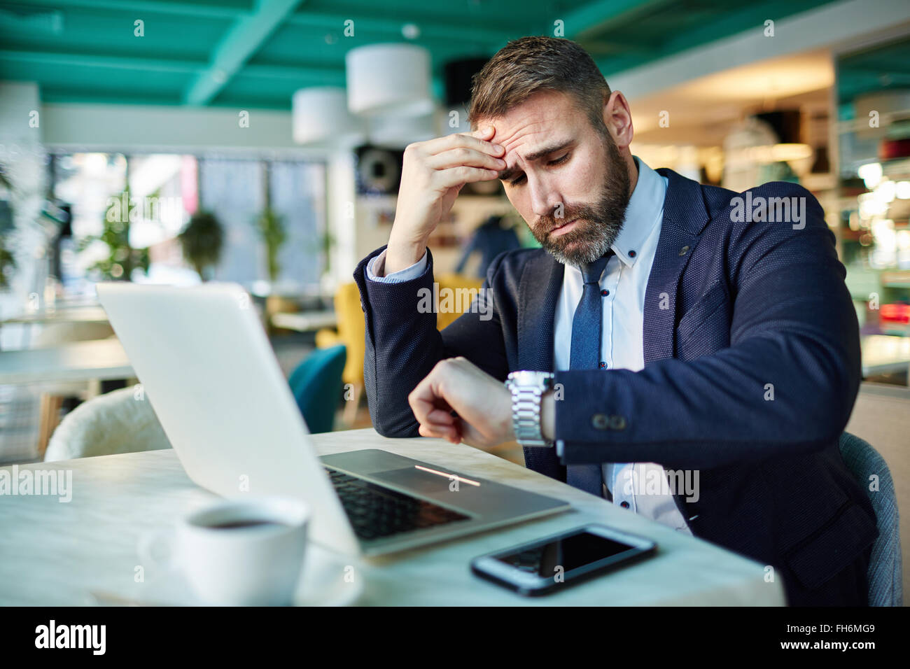 Contemporary businessman looking at watch - Stock Image