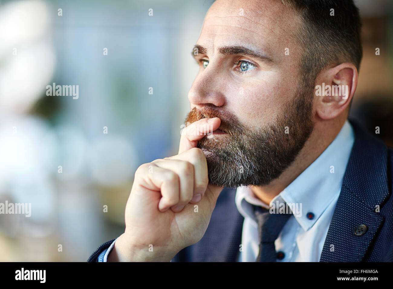 Pensive man touching his chin - Stock Image