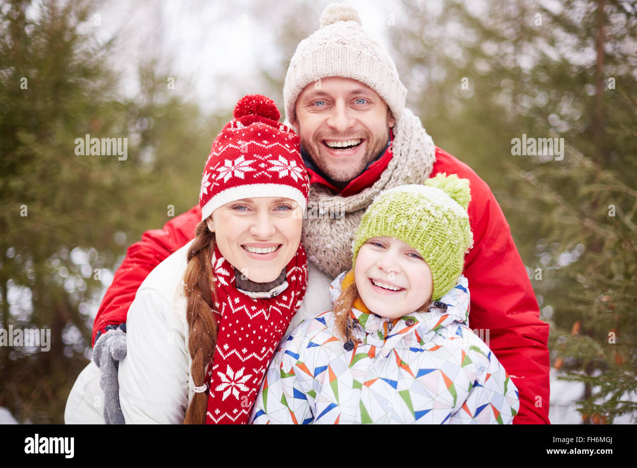Happy family looking at camera with toothy smiles outdoors - Stock Image