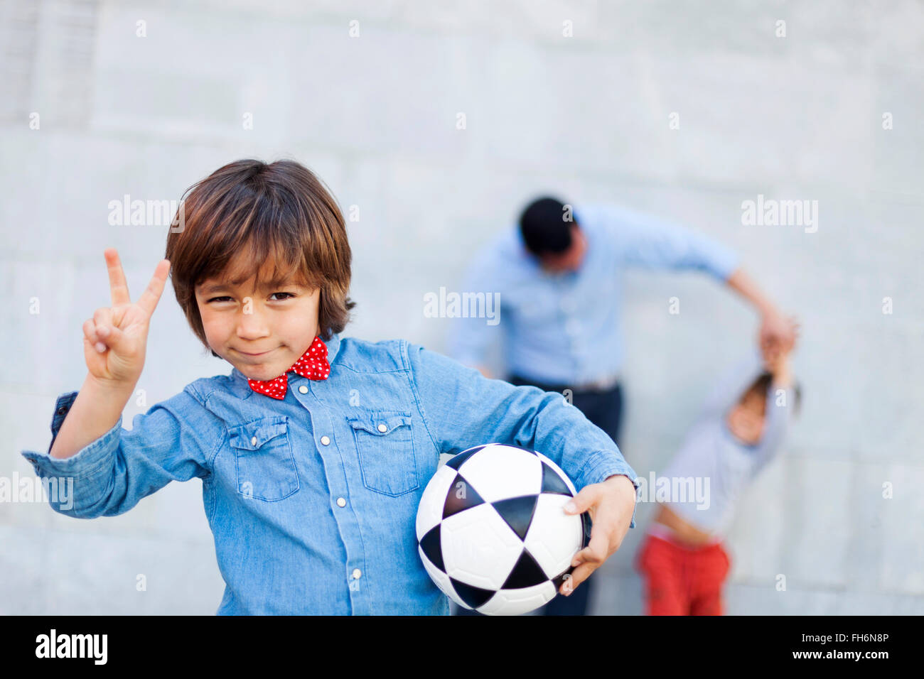 Boy holding soccer ball and making victory sign, family playing in background - Stock Image