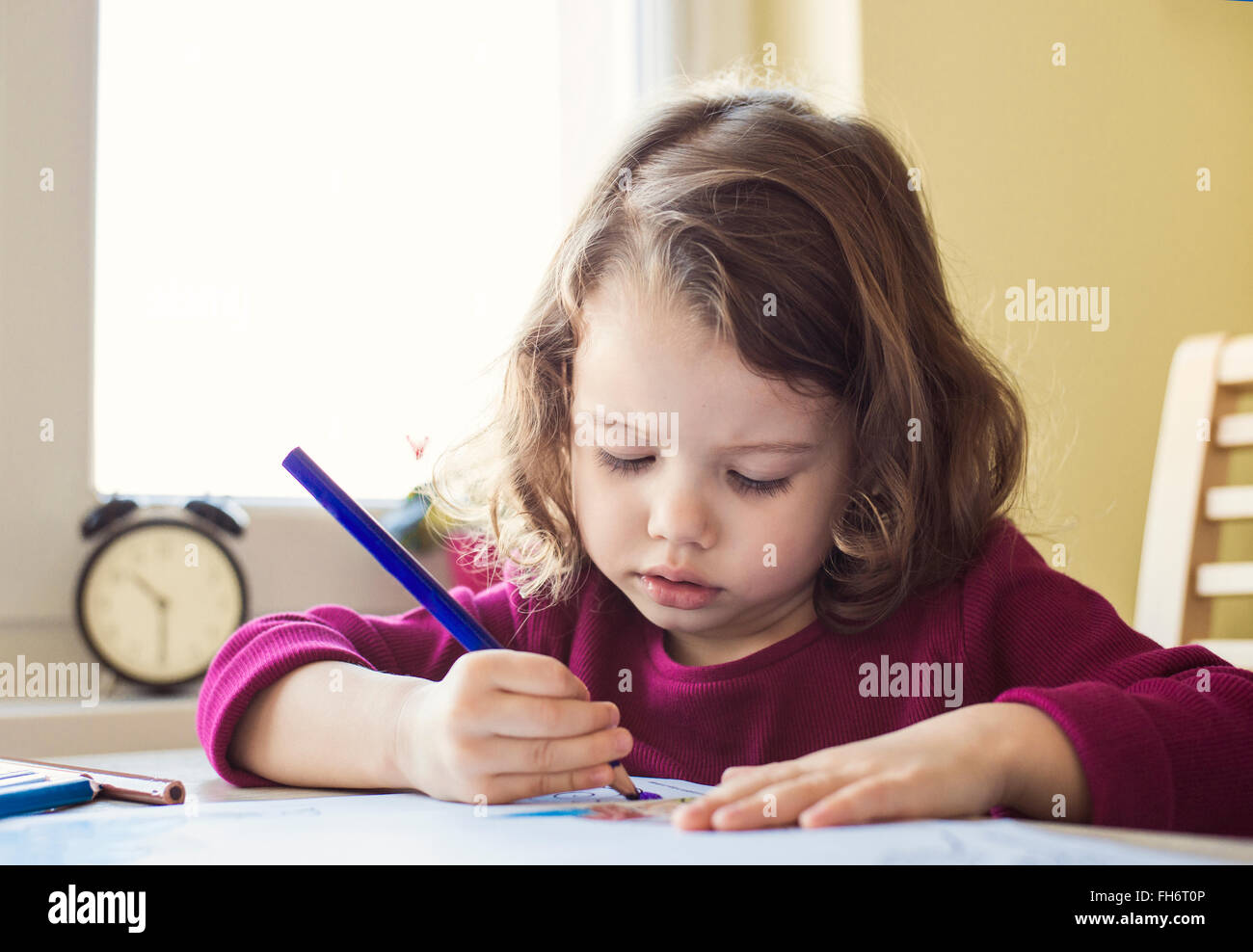 Portrait of little girl painting with coloured pencil - Stock Image