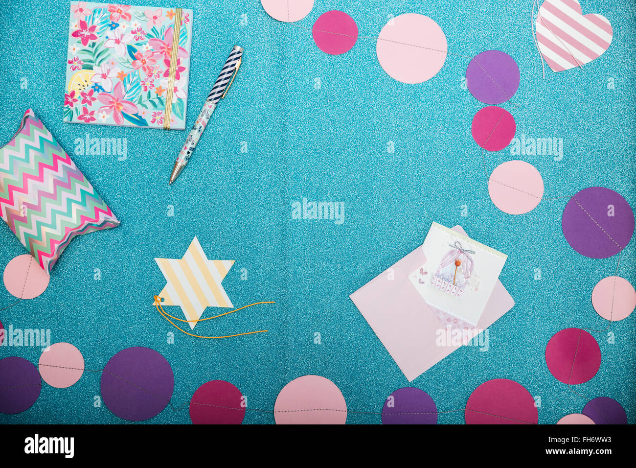 Top view of colorful decorations, notepad, pen and present box on shining turquoise backgound - Stock Image