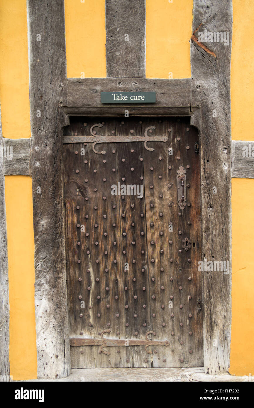 A 'Take Care' sign above a door at Stokesay Castle. In Stokesay, Ludlow, England. - Stock Image