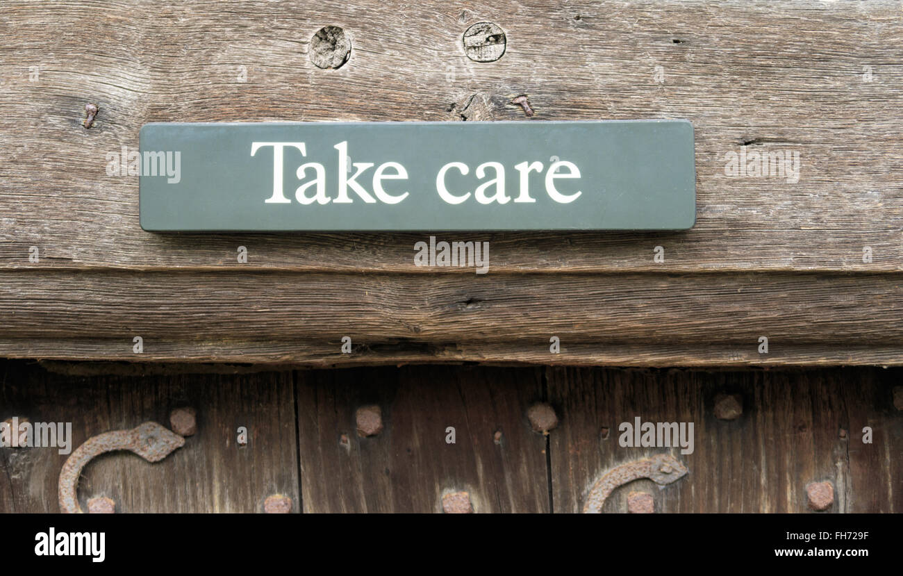 A 'Take Care' sign above a doorway at Stokesay Castle. In Stokesay, Ludlow, England. On 21st Fe - Stock Image