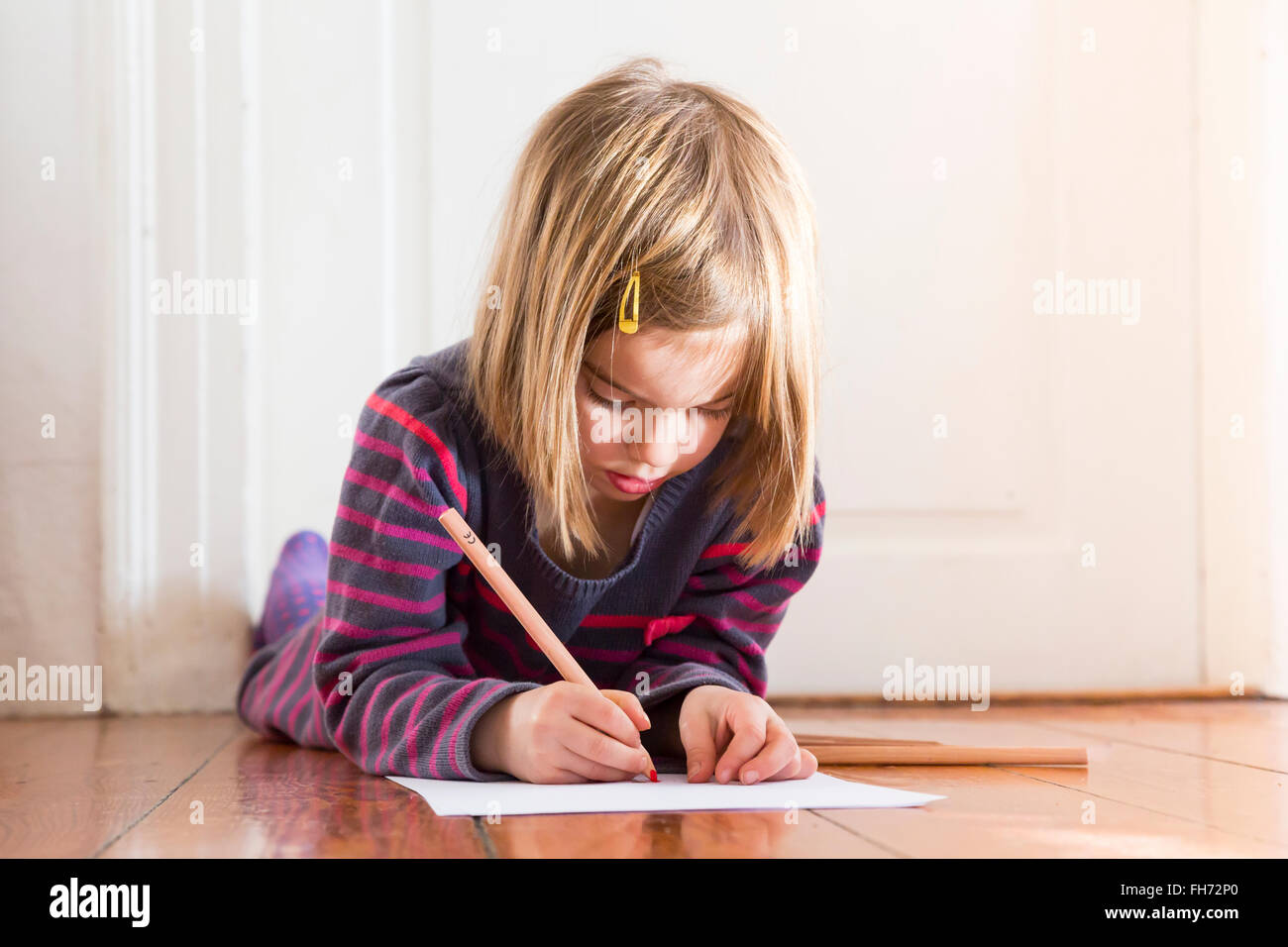 Little girl lying on the floor drawing something - Stock Image