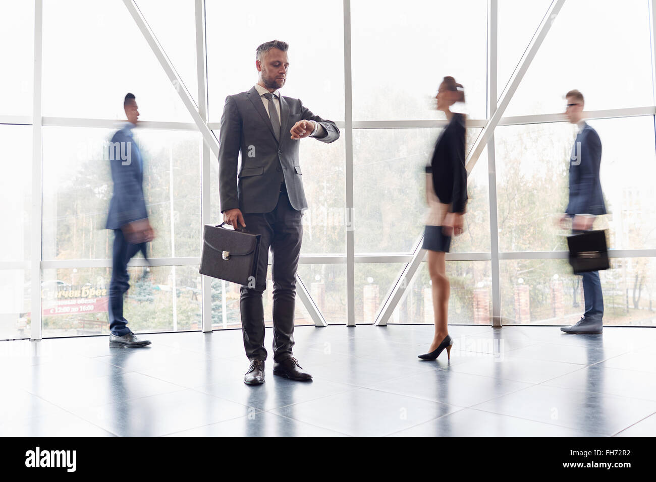 Serious businessman with briefcase looking at watch with hurrying people near by - Stock Image