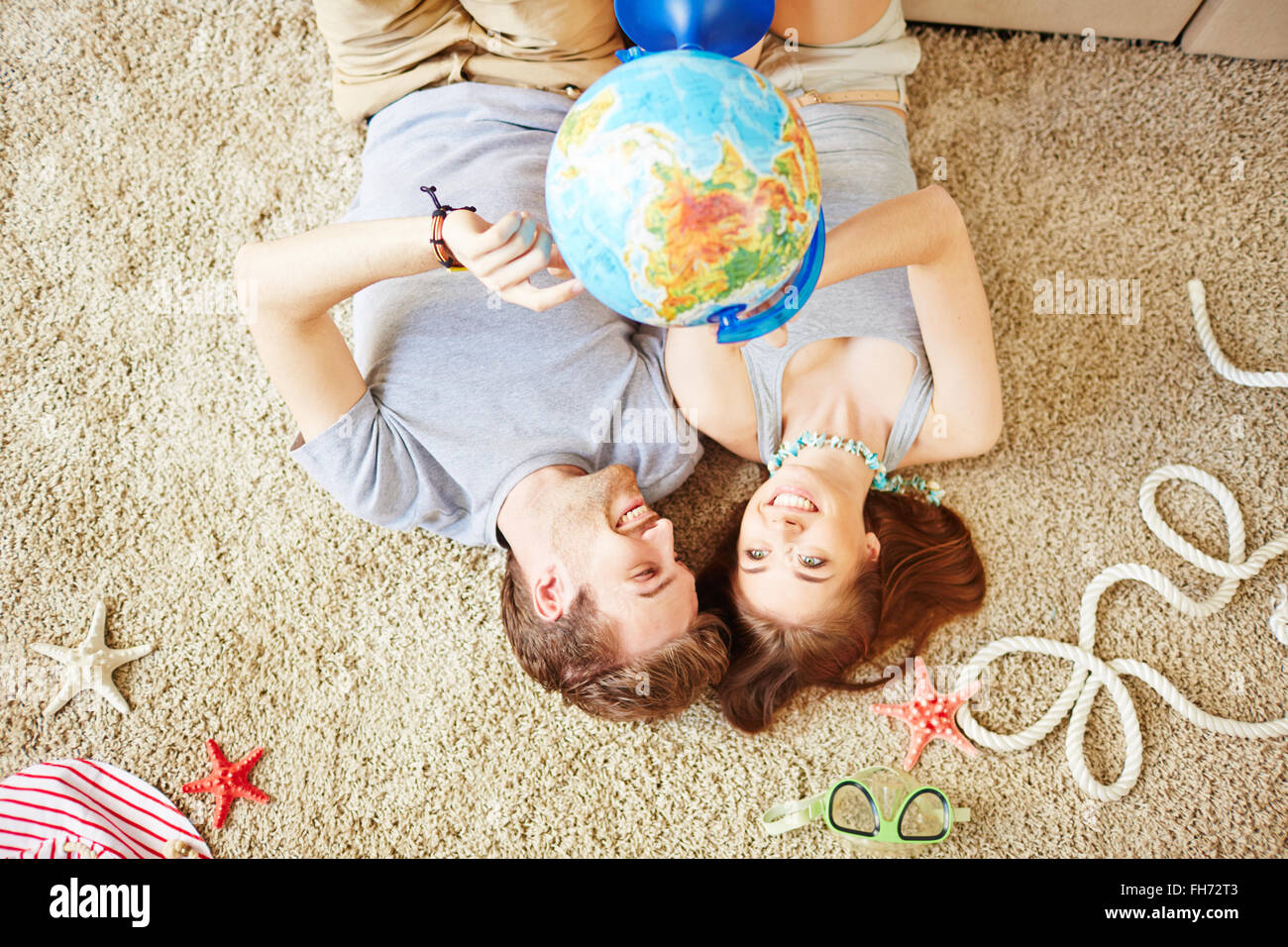 Restful young couple with globe lying on the floor at home - Stock Image