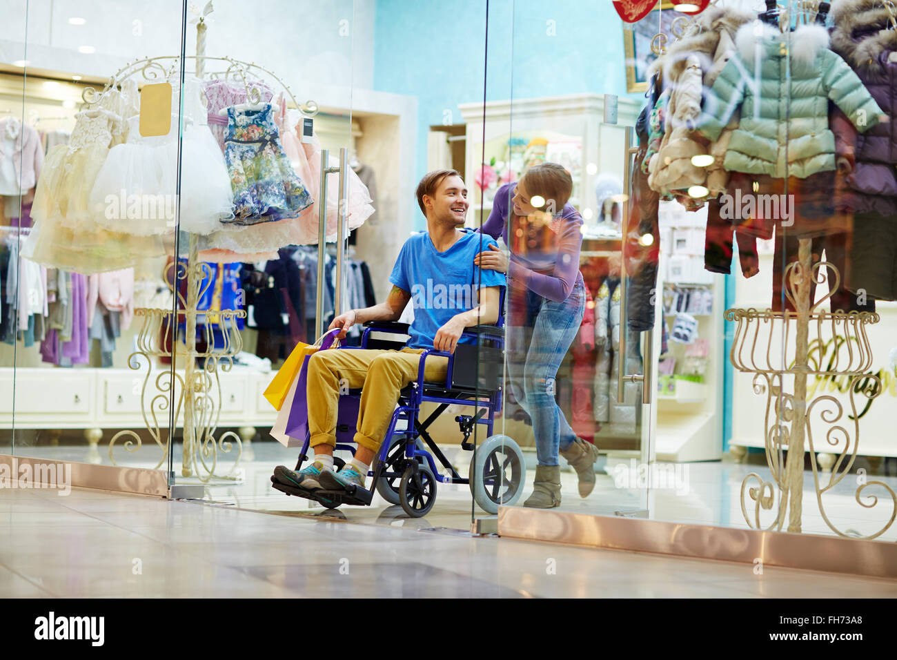 Caring girl and her disable boyfriend visiting clothing department in the mall - Stock Image