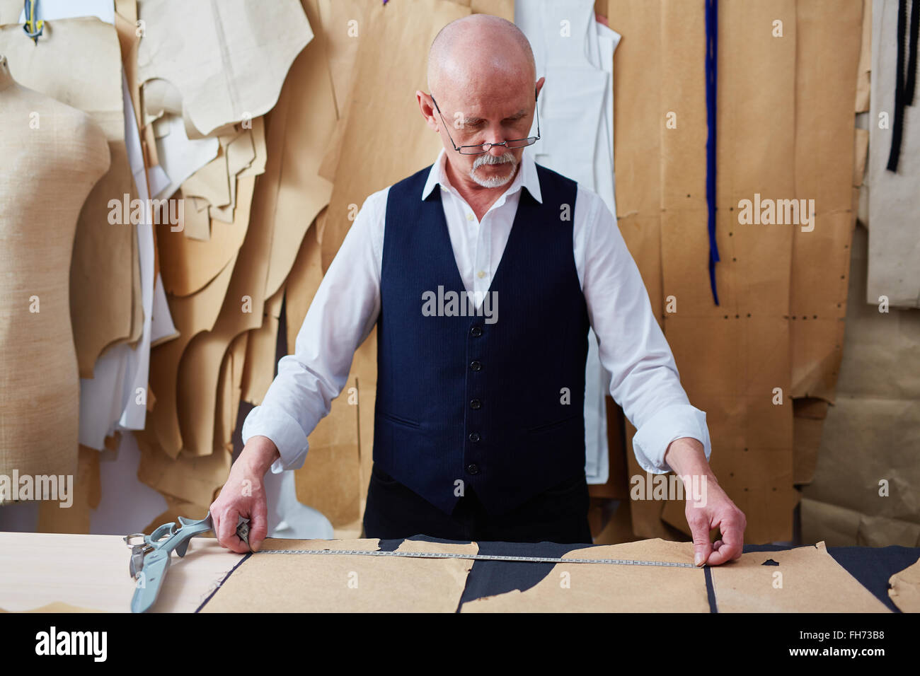 Mature tailor working with patterns and measuring tape - Stock Image