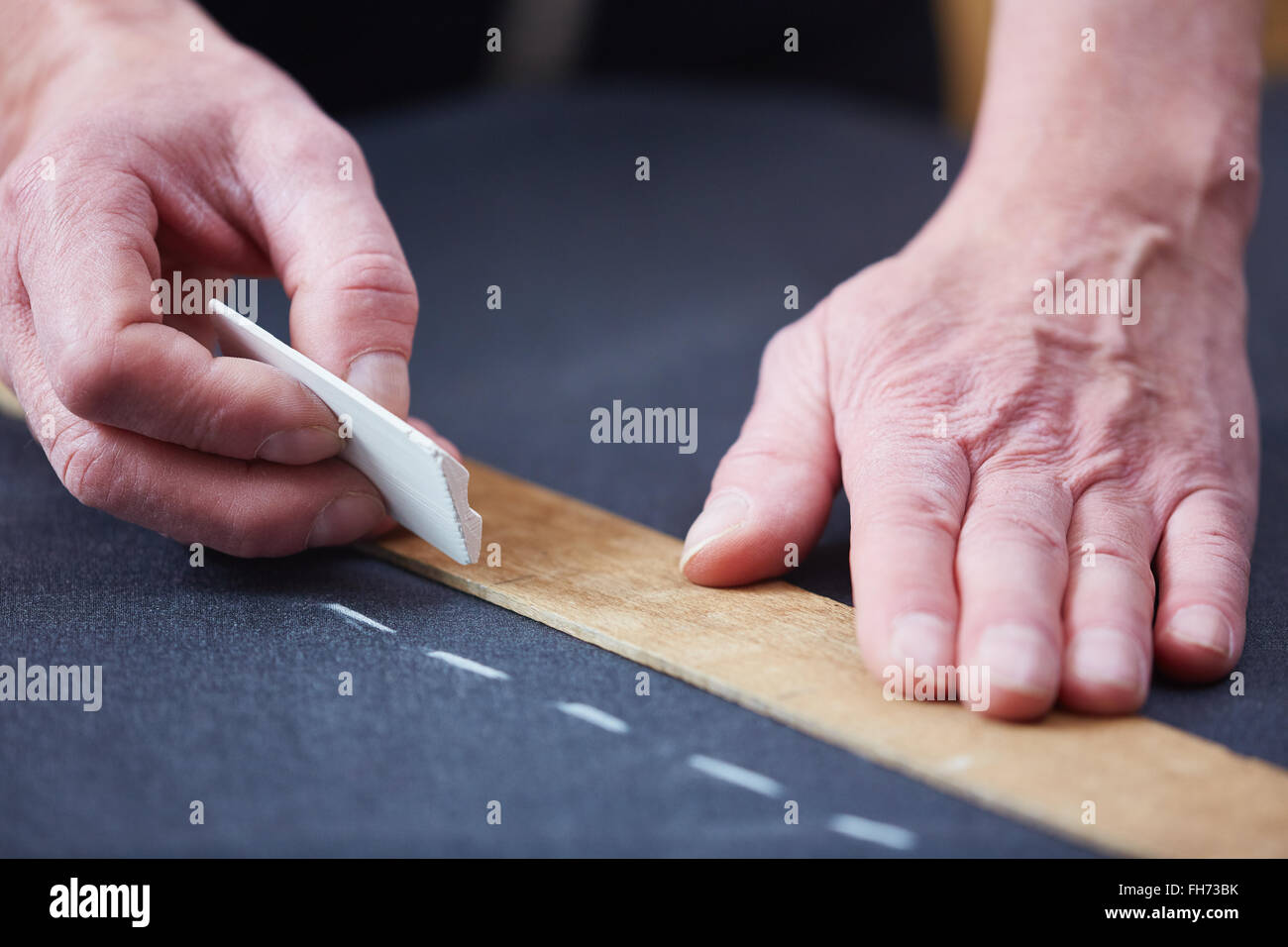 Hands of tailor dotting with chalk on textile Stock Photo