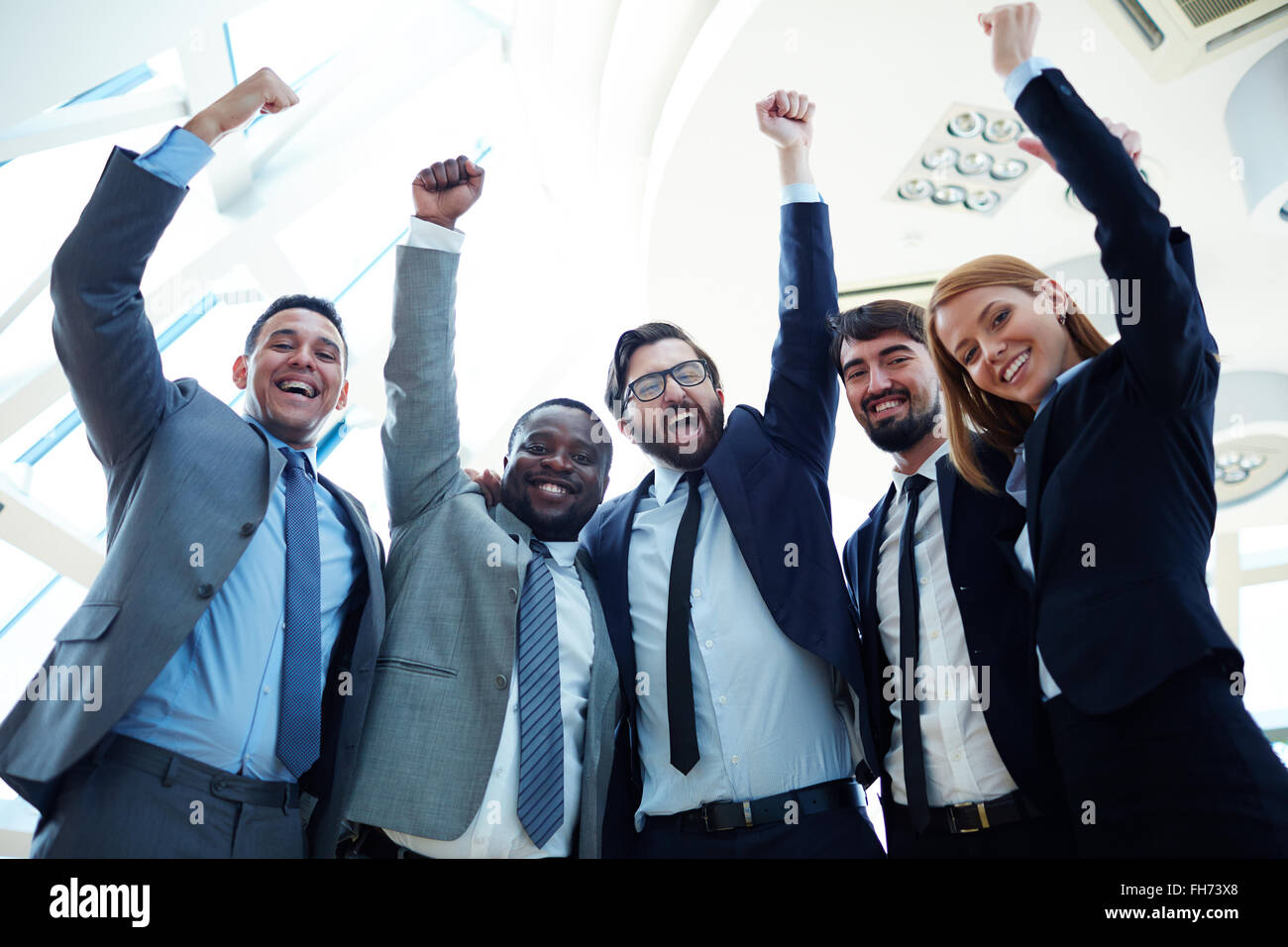 Ecstatic business partners in suits raising their arms and expressing triumph - Stock Image