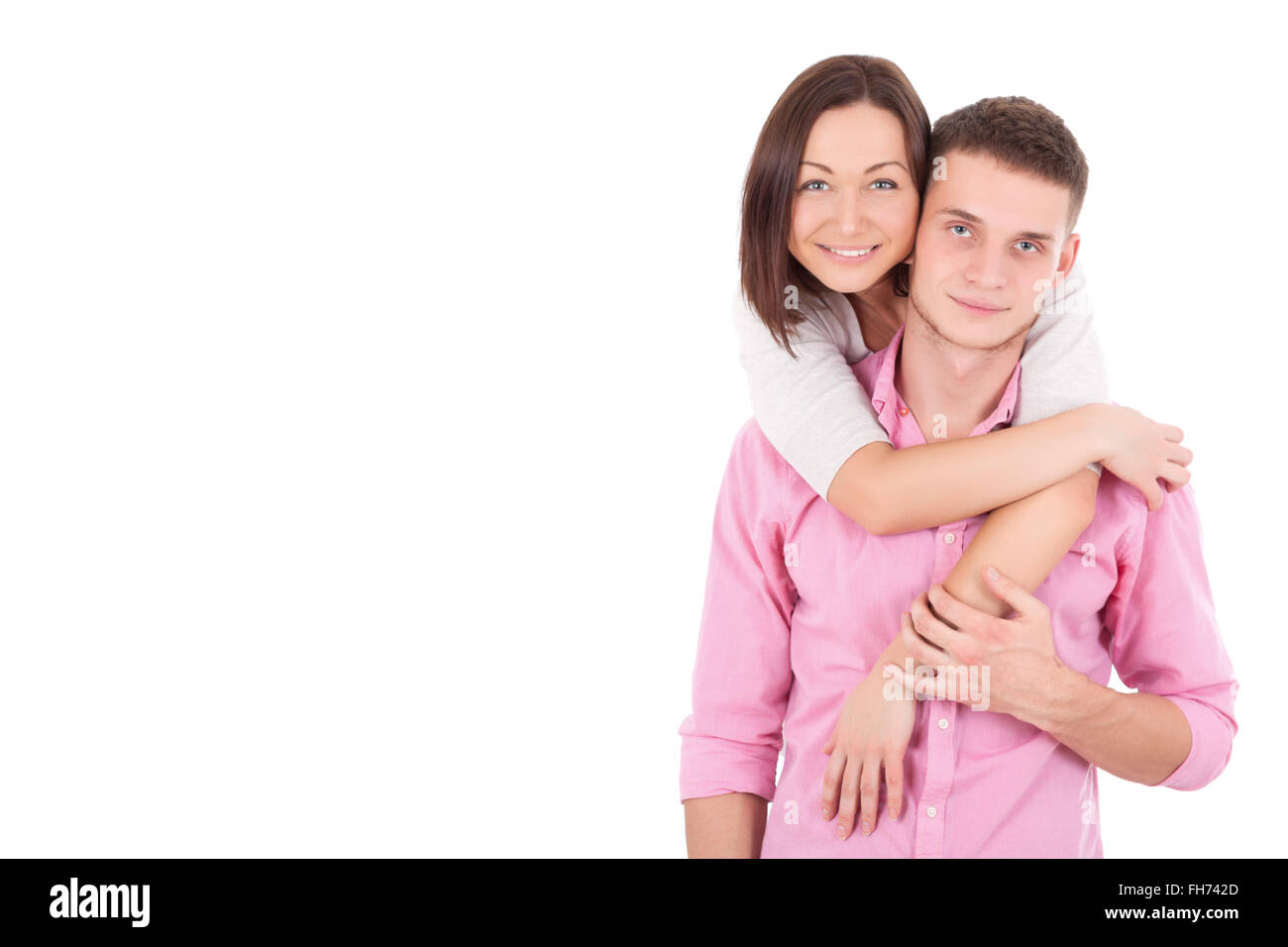 A young heterosexual couple, possibly just married, a wife and a husband standing together, hugging and holding - Stock Image
