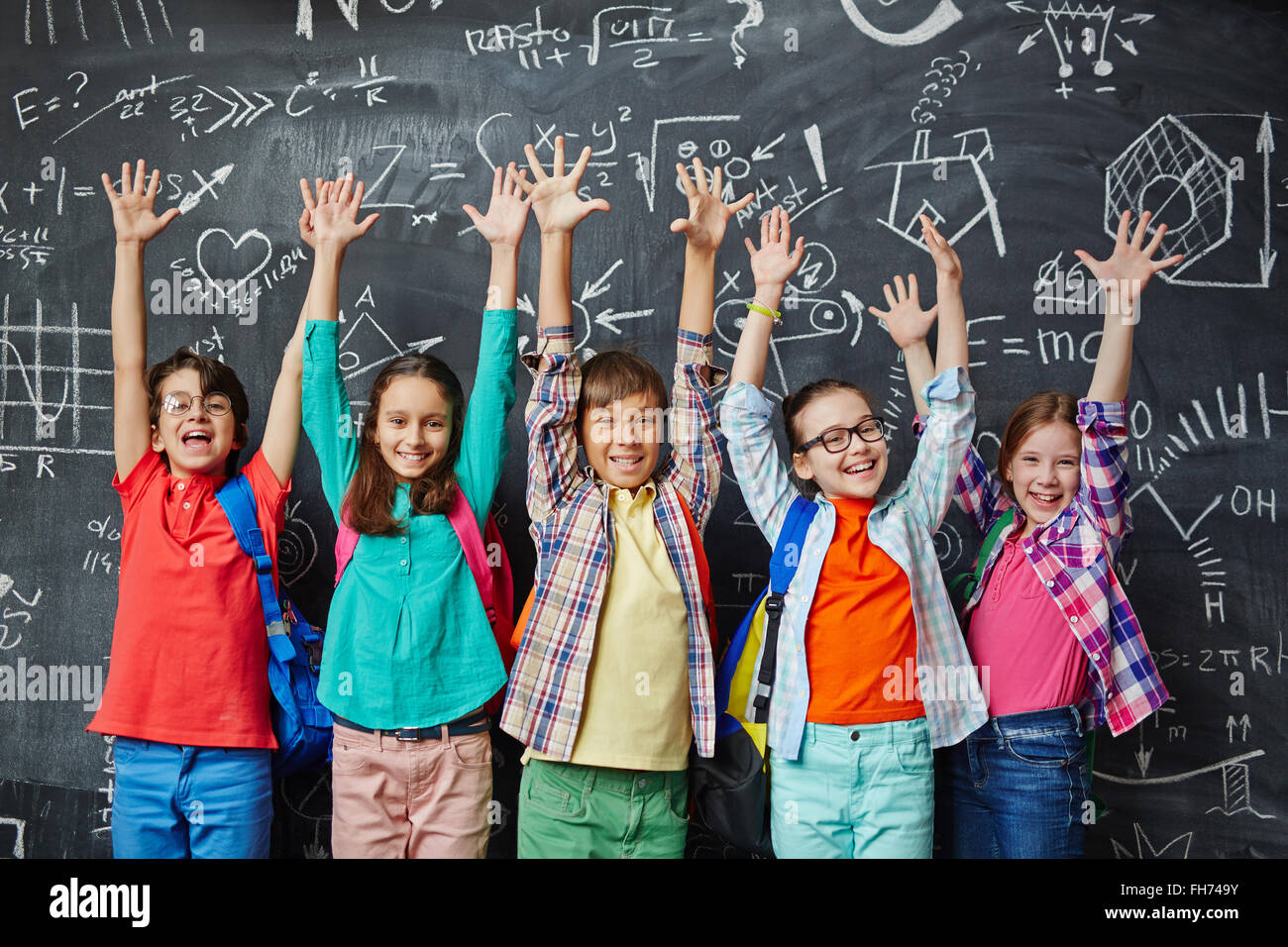 Ecstatic learners raising hands against blackboard - Stock Image