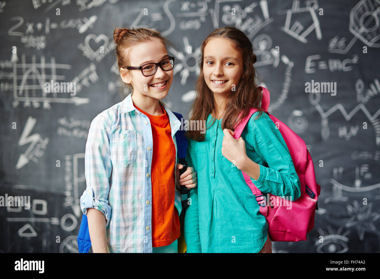 Adorable schoolmates with backpacks looking at camera Stock Photo