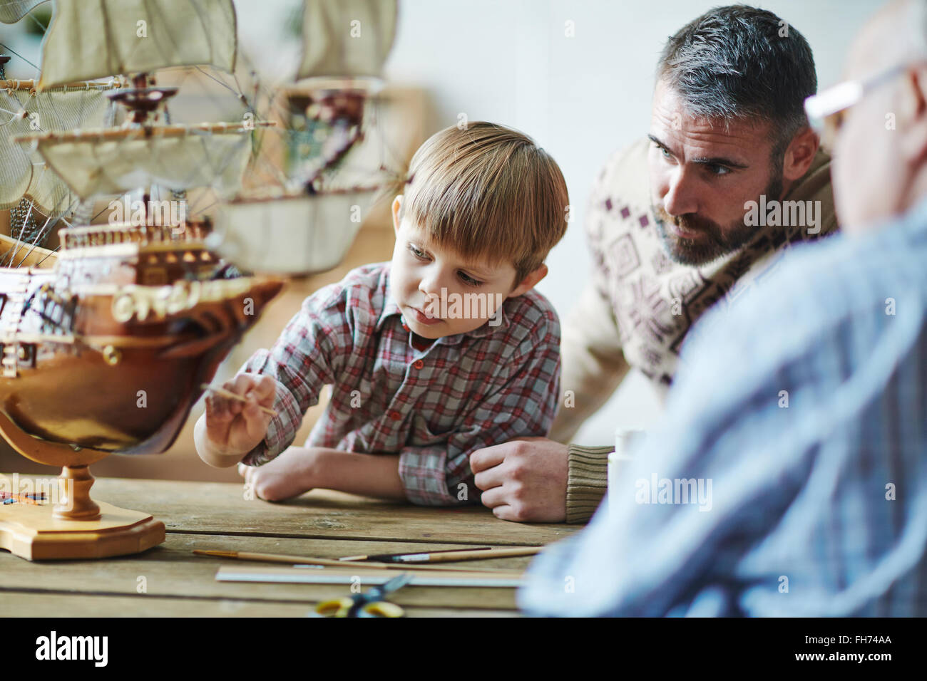 Adorable youngster painting toy ship with his father and grandfather near by - Stock Image