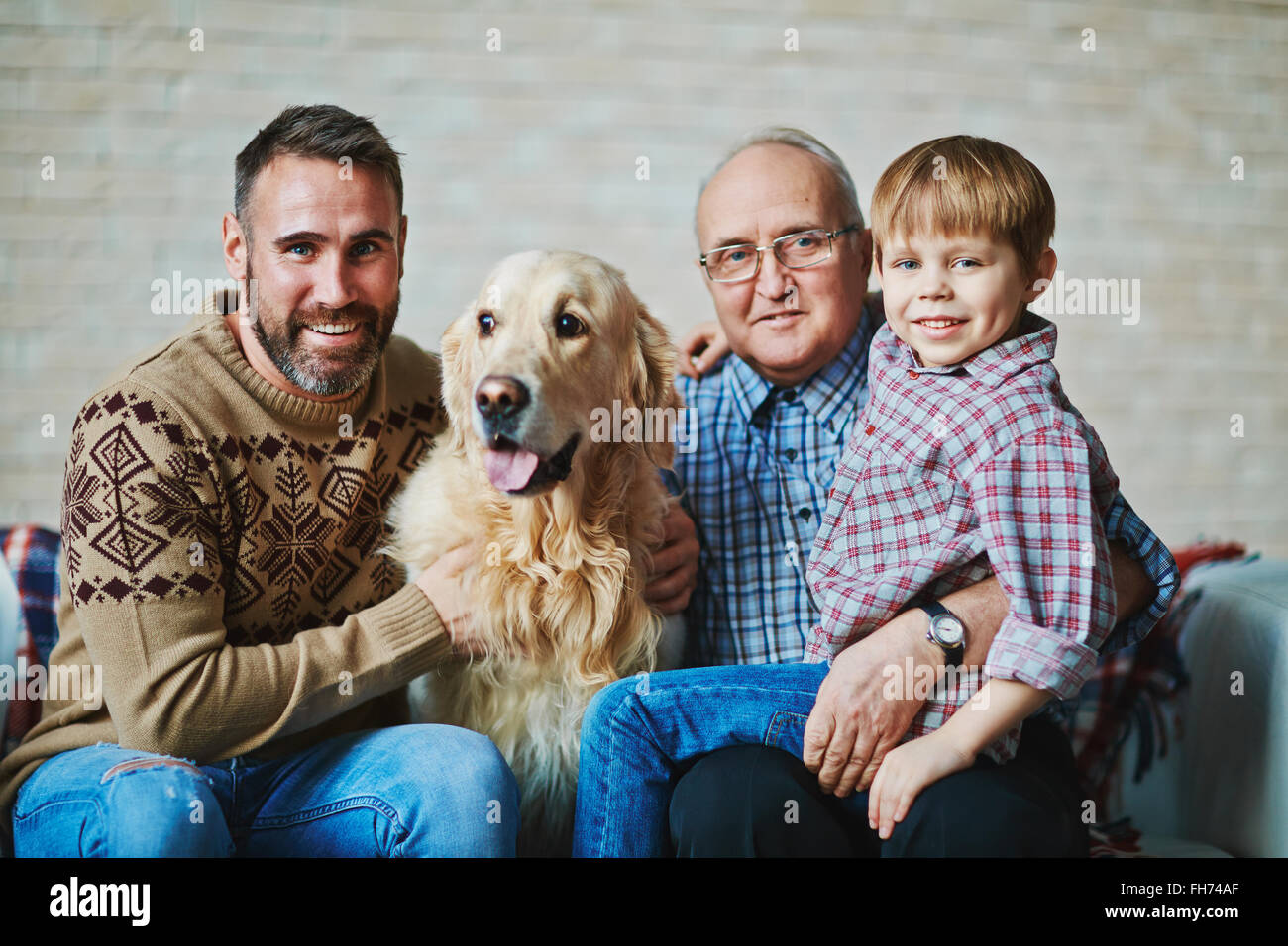 Mature and young men, youngster in casual-wear and fluffy pet looking at camera - Stock Image
