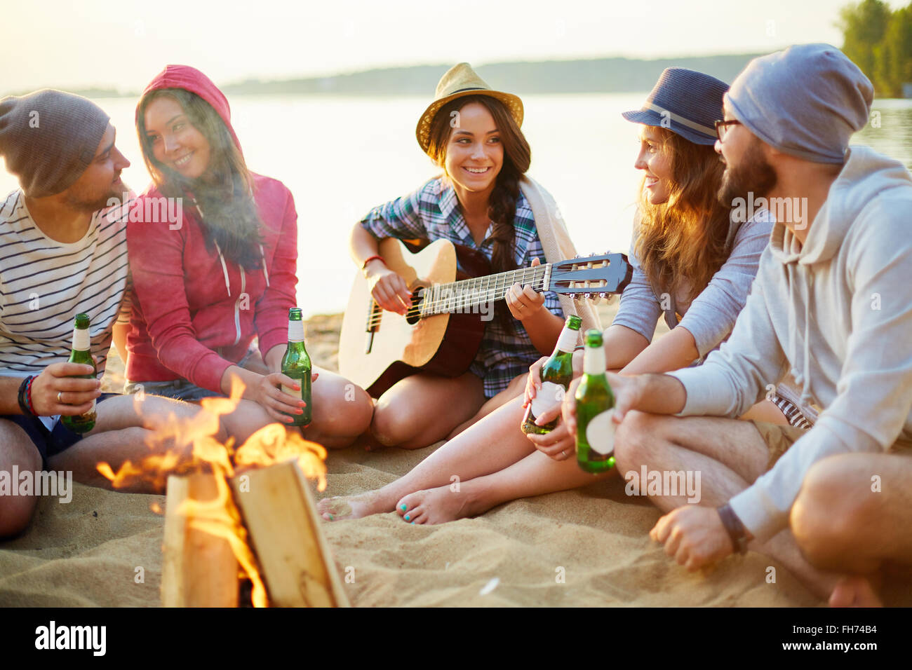 Happy friends with drinks talking by campfire - Stock Image