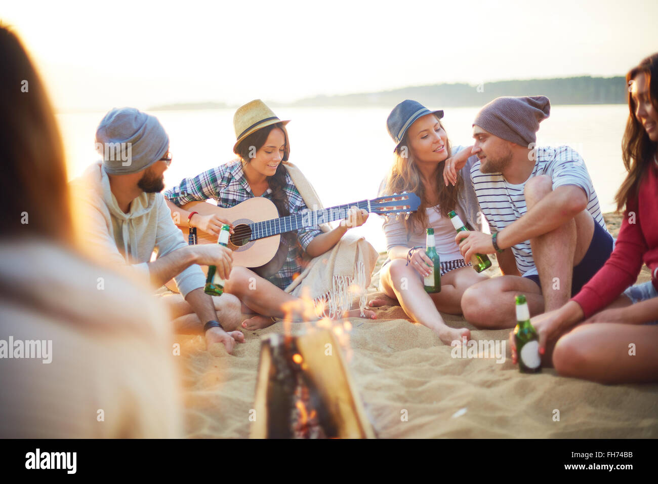 Happy friends with drinks sitting on sand around campfire - Stock Image