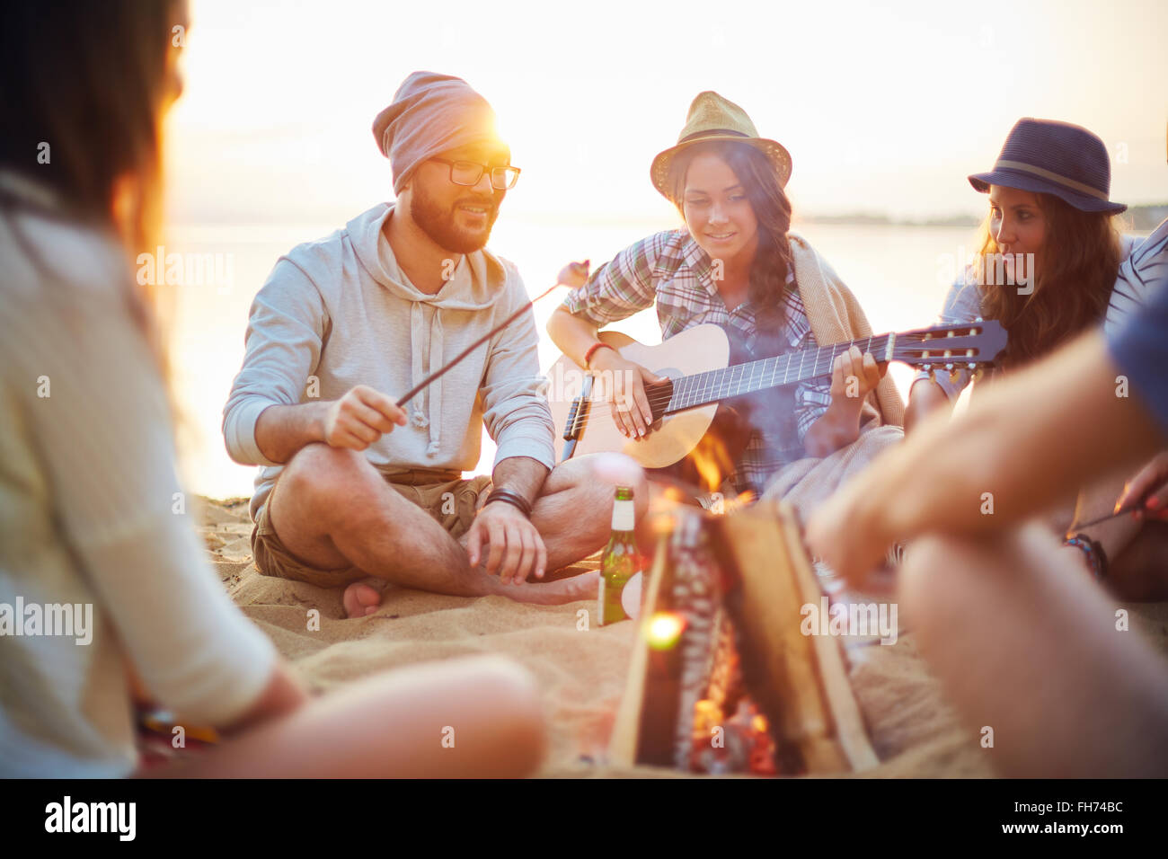 Group of campers spending evening by campfire - Stock Image