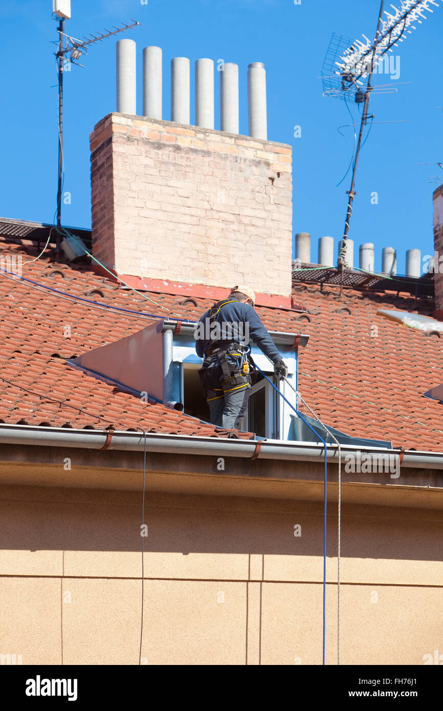 Maintenance Worker with Safety Strap on a House Roof - Stock Image