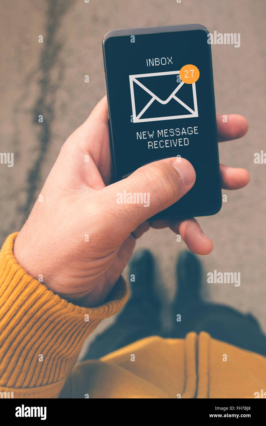 Using mobile smartphone to access e-mail inbox, man viewing incoming messages while walking on street, top view, - Stock Image