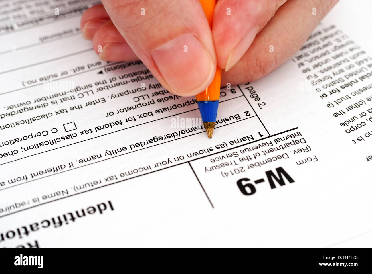 Person Hand With Pen Filling In Form W 9 Request For Taxpayer Stock