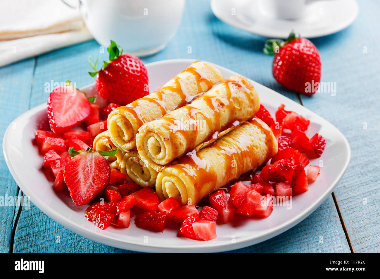 rolled pancakes with strawberries and caramel breakfast - Stock Image