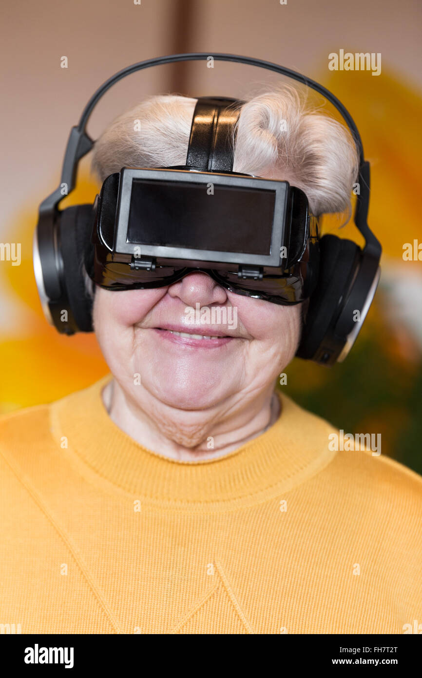 funny senior adult with virtual reality glasses is having fun