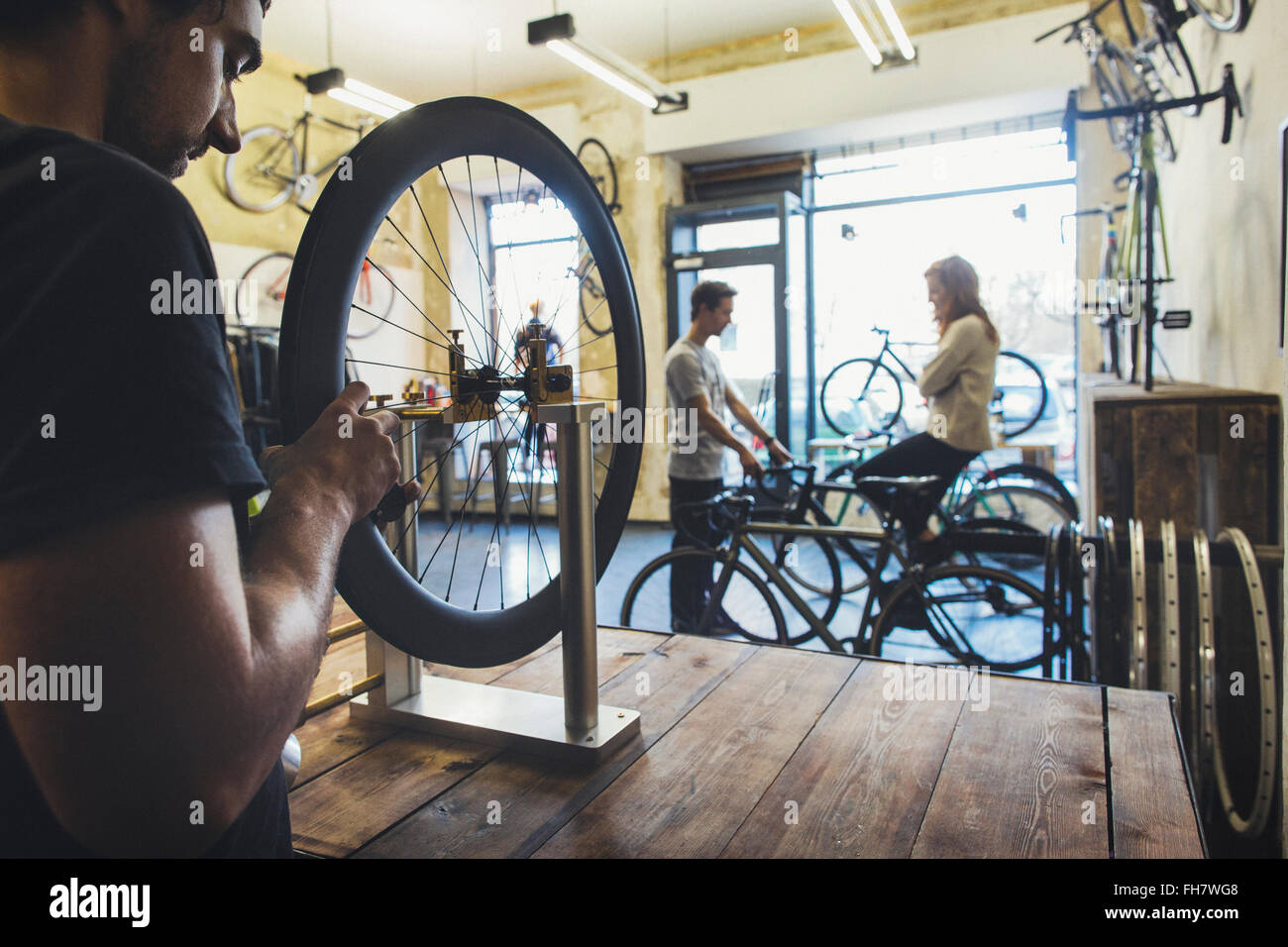 Mechanic, salesman and client in a custom-made bicycle store - Stock Image