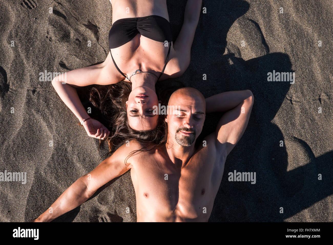 Spain, Tenerife, portrait of couple sunbathing on the beach - Stock Image