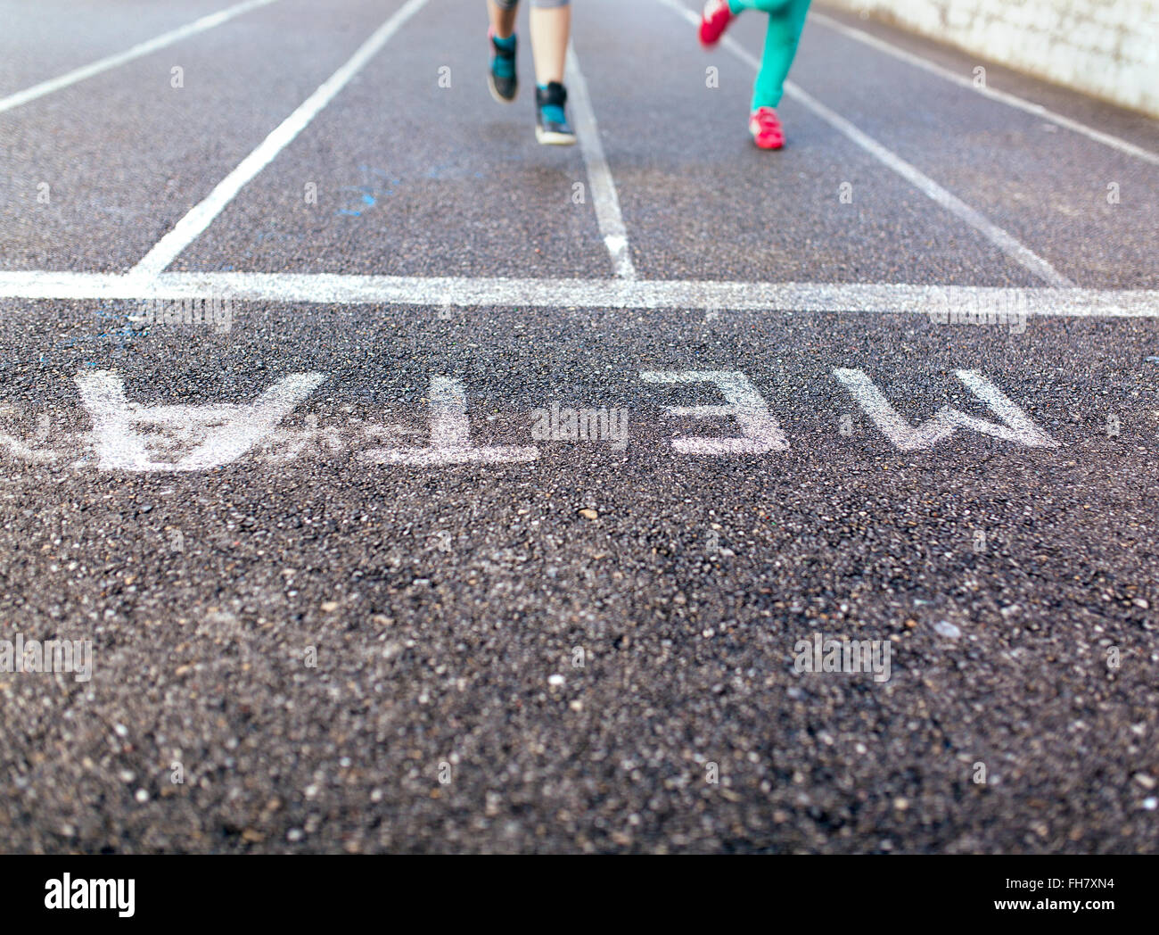 Legs of two running girls on tarmac - Stock Image